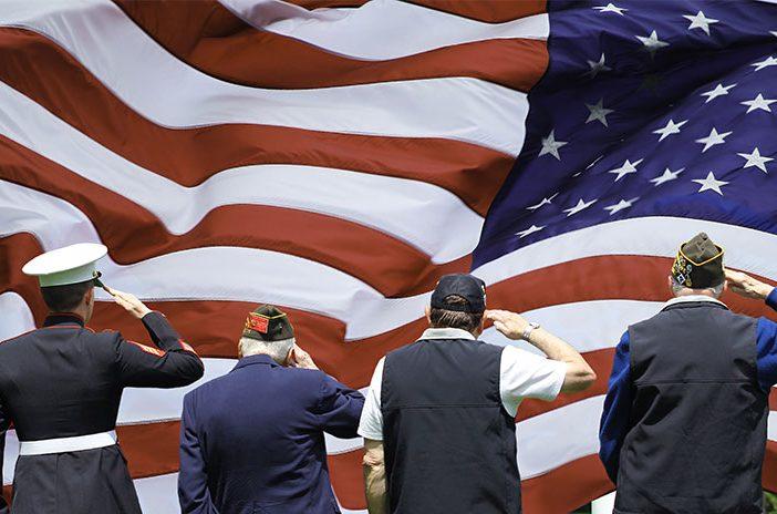 Four veterans saluting American flag
