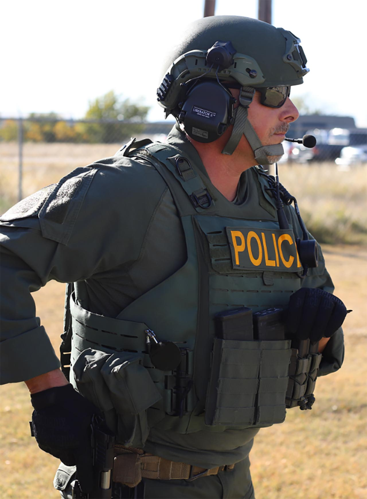 Man in police protective gear with his hand on his holstered Staccato handgun