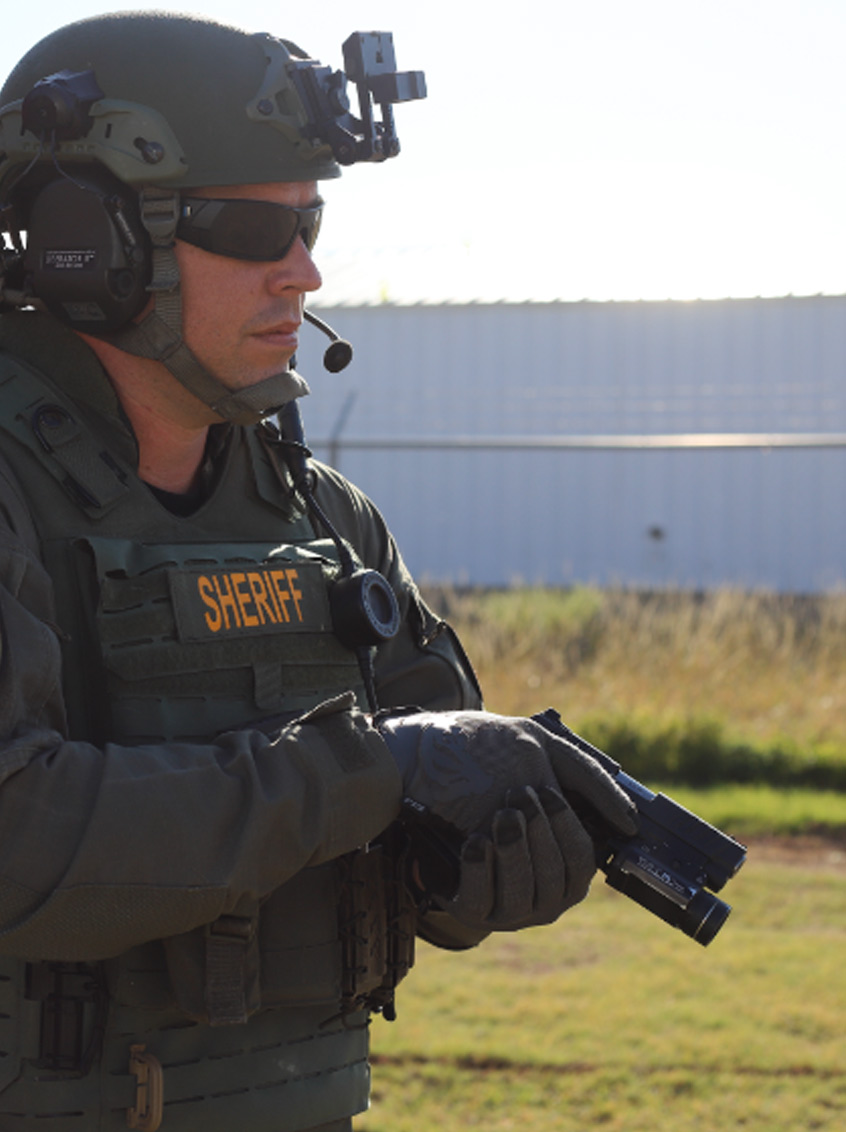 Man in sheriff protective gear holding a Staccato handgun