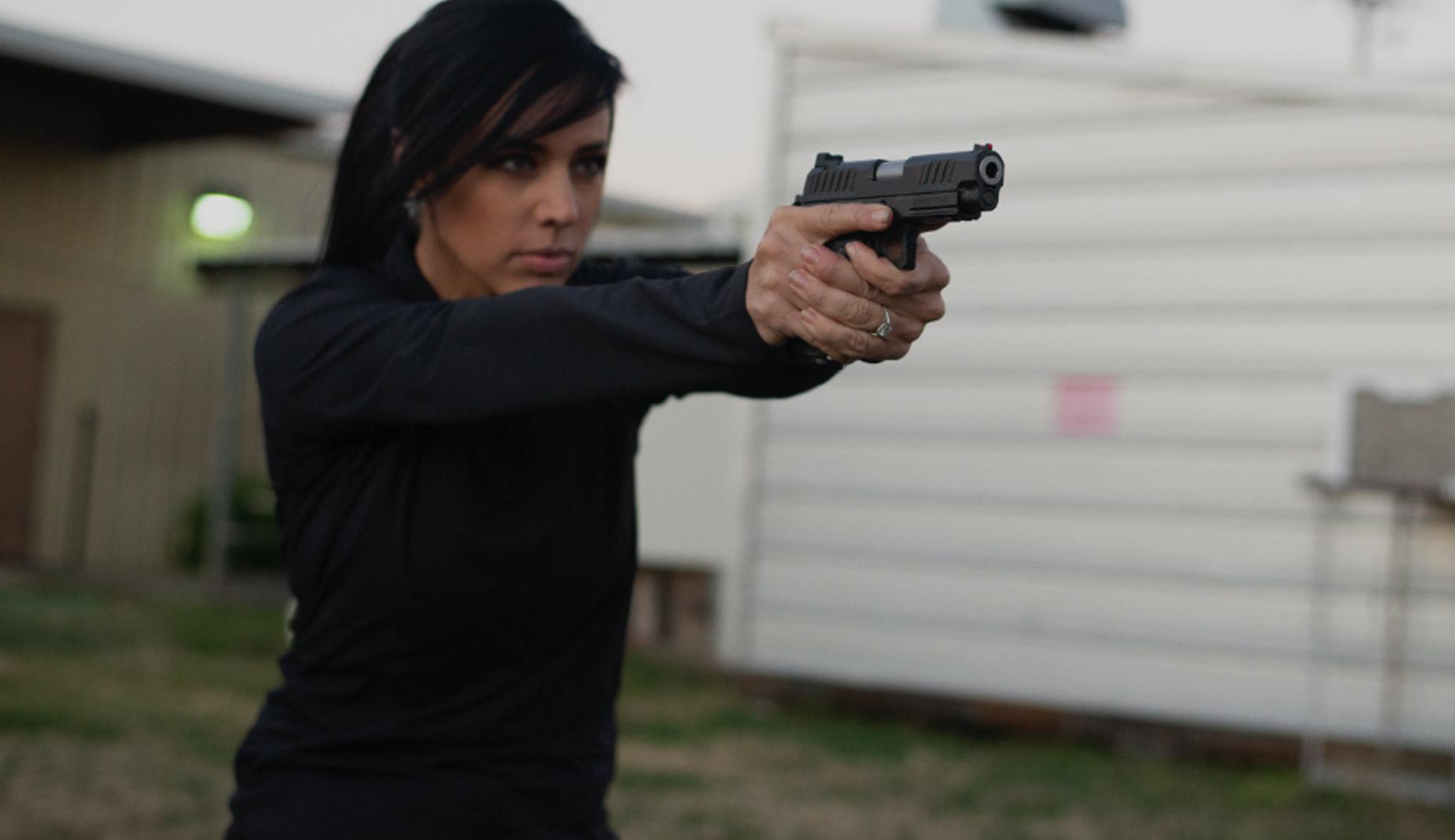 Woman aiming staccato handgun outdoors