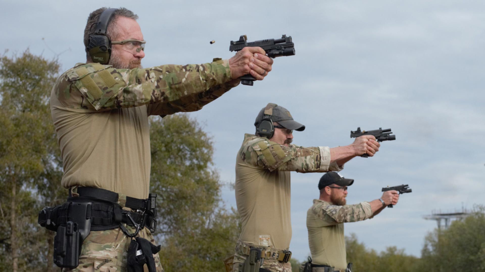 Three men in camouflage firing Staccato handguns at the range