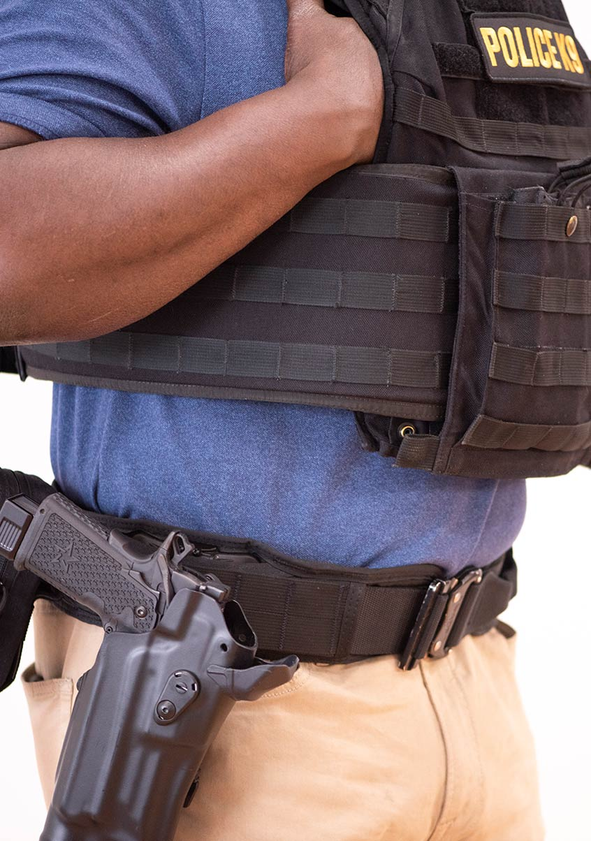 Man in police protective gear with a holstered Staccato handgun
