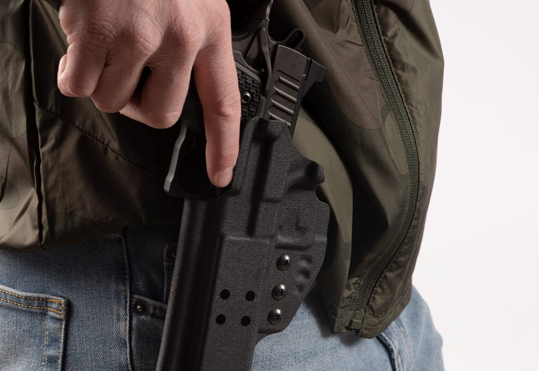 Individual with hand on holstered Staccato handgun