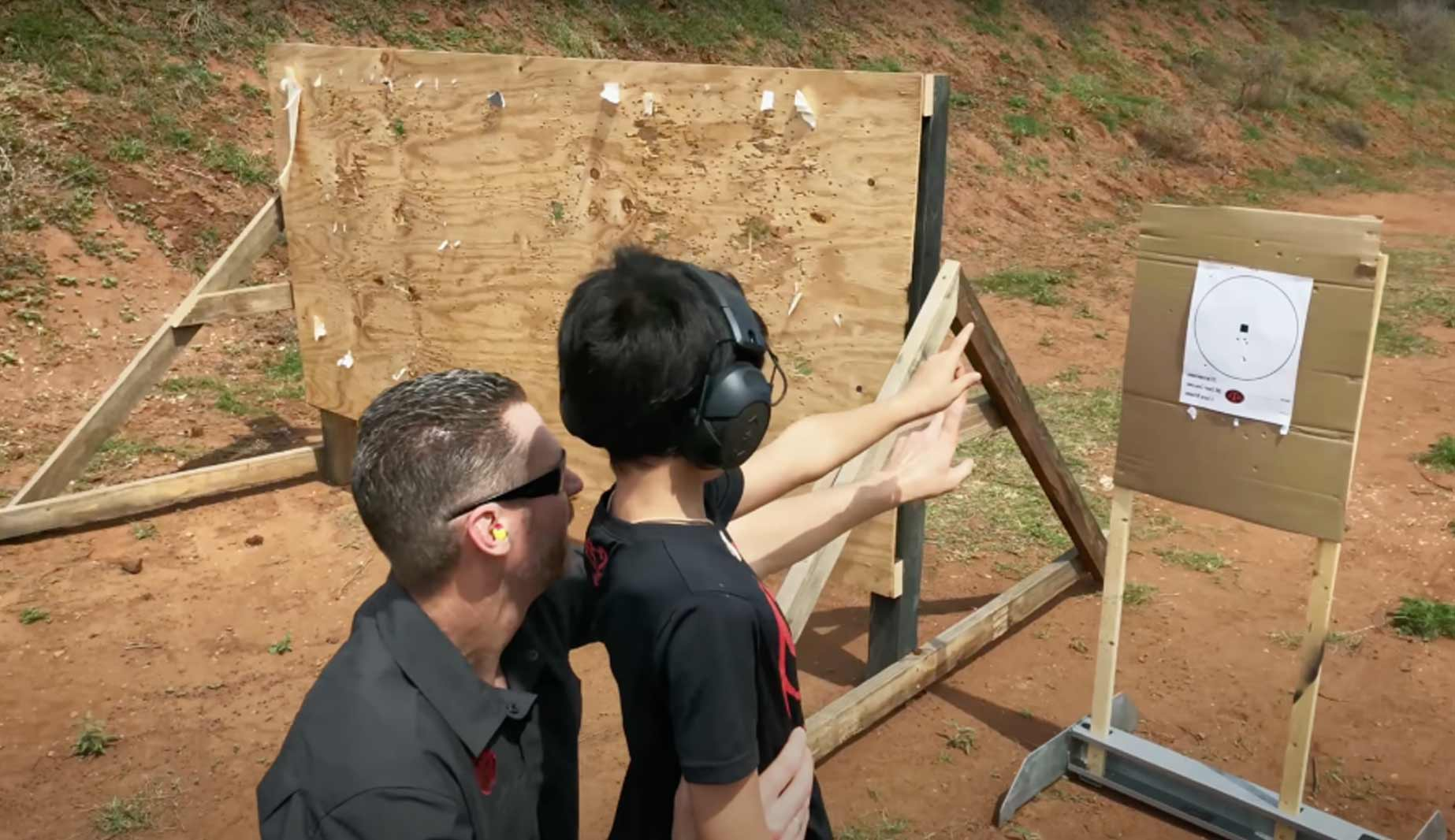 Instructor helping a new shooter child with his grouping
