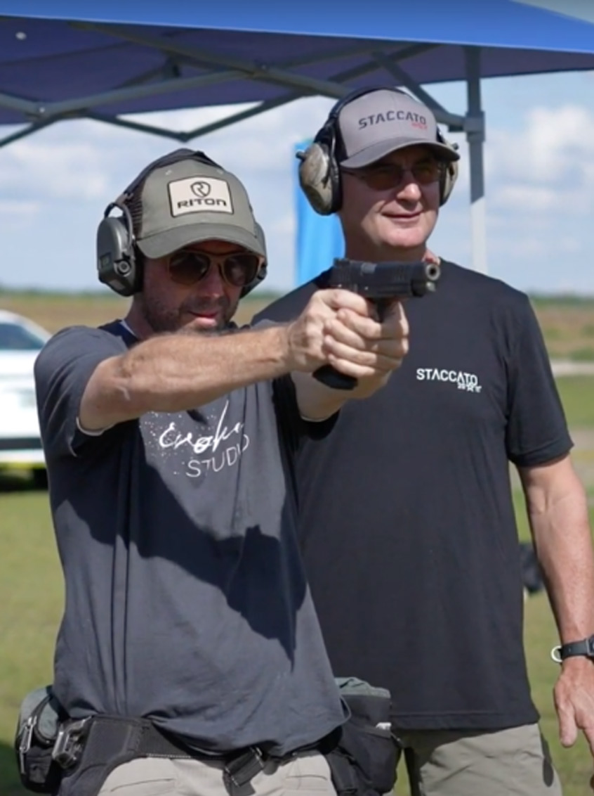 New shooter aiming Staccato handgun with instructor by his side