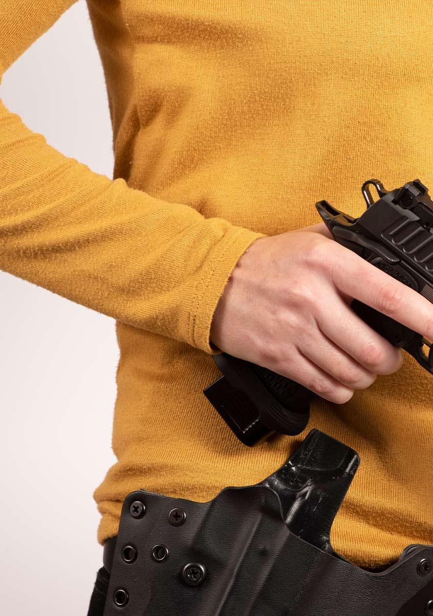 Hand gripping Staccato handgun