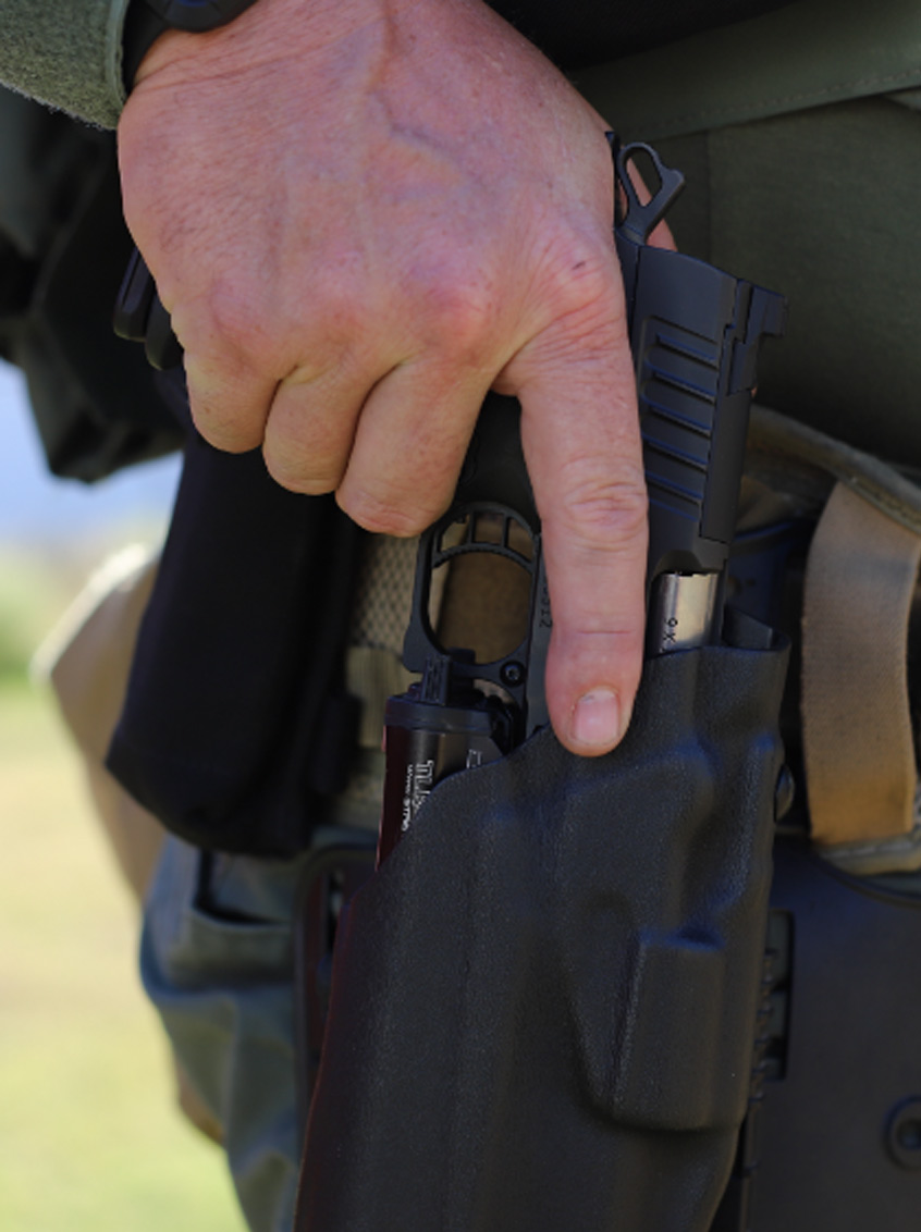 Hand removing a Staccato handgun from the holster