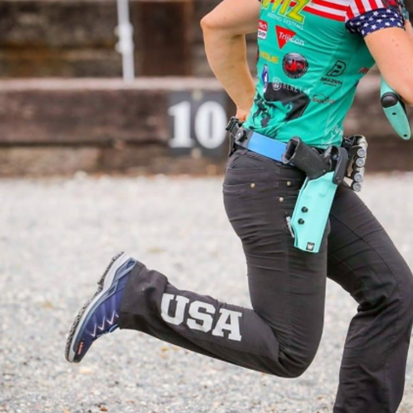 Individual running at competition event with holstered Staccato handgun