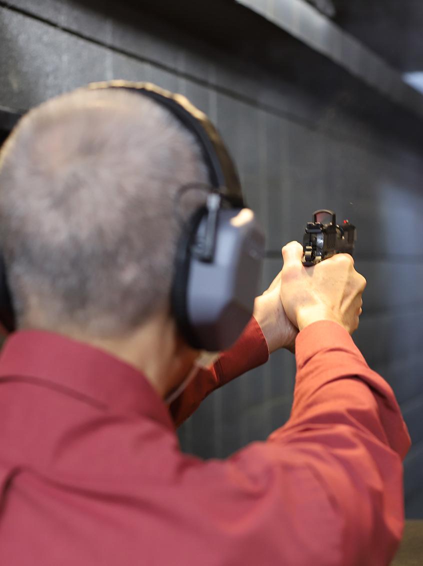 Man shooting Staccato handgun at an indoor shooting range