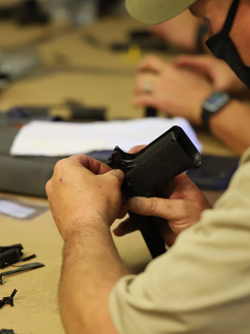 Man inspecting a Staccato handgun near the rear sight