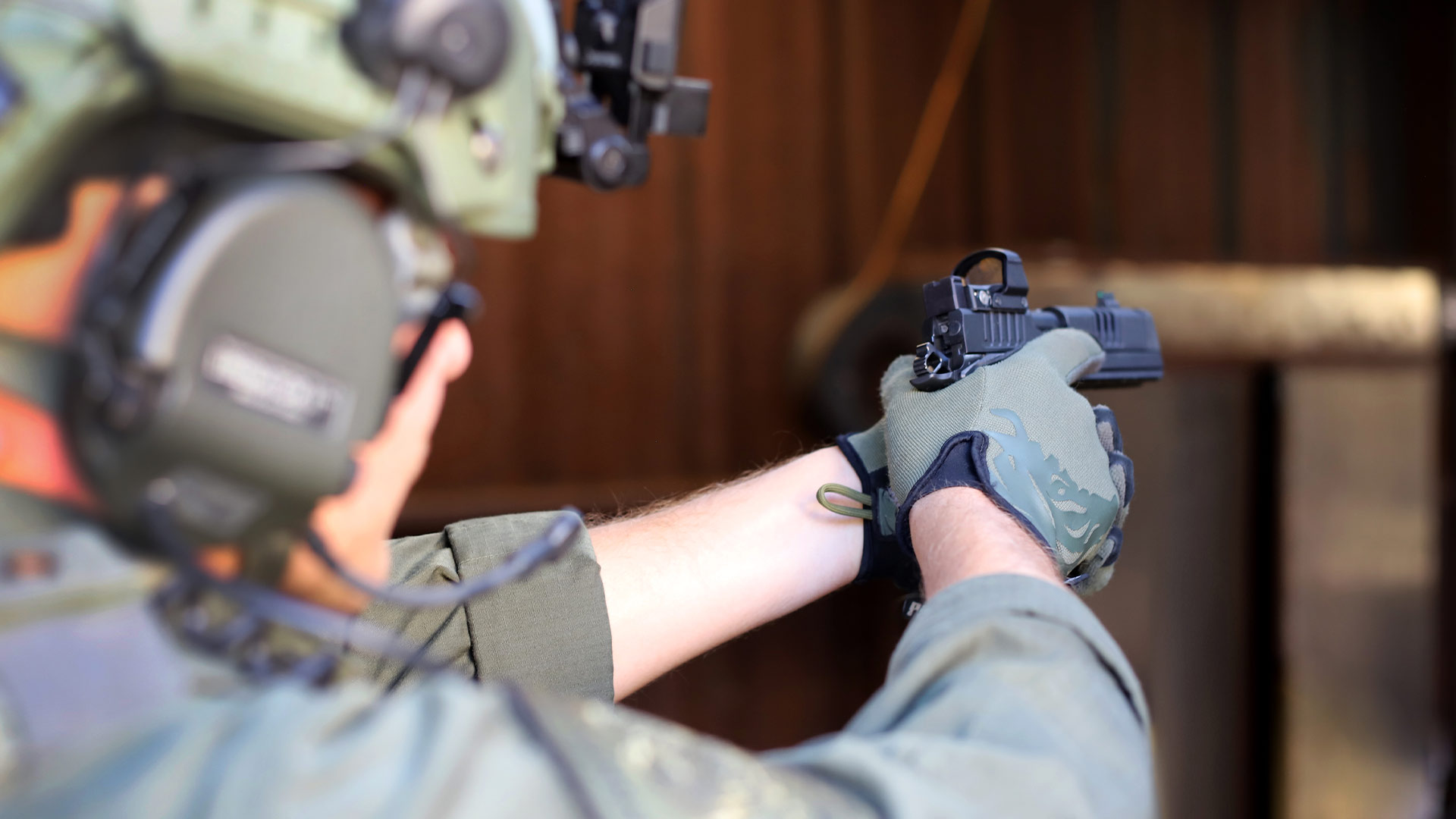 Man in tactical gear aiming Staccato handgun with optic sight