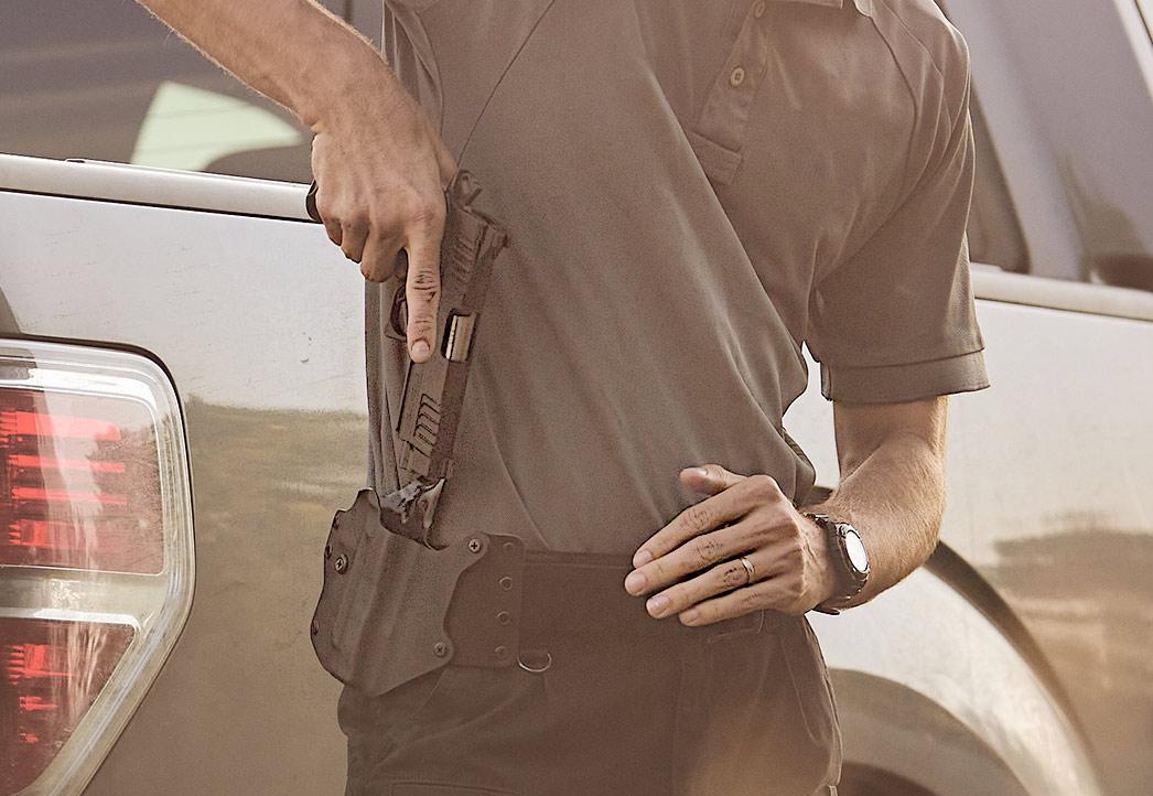 Man drawing holstered Staccato handgun