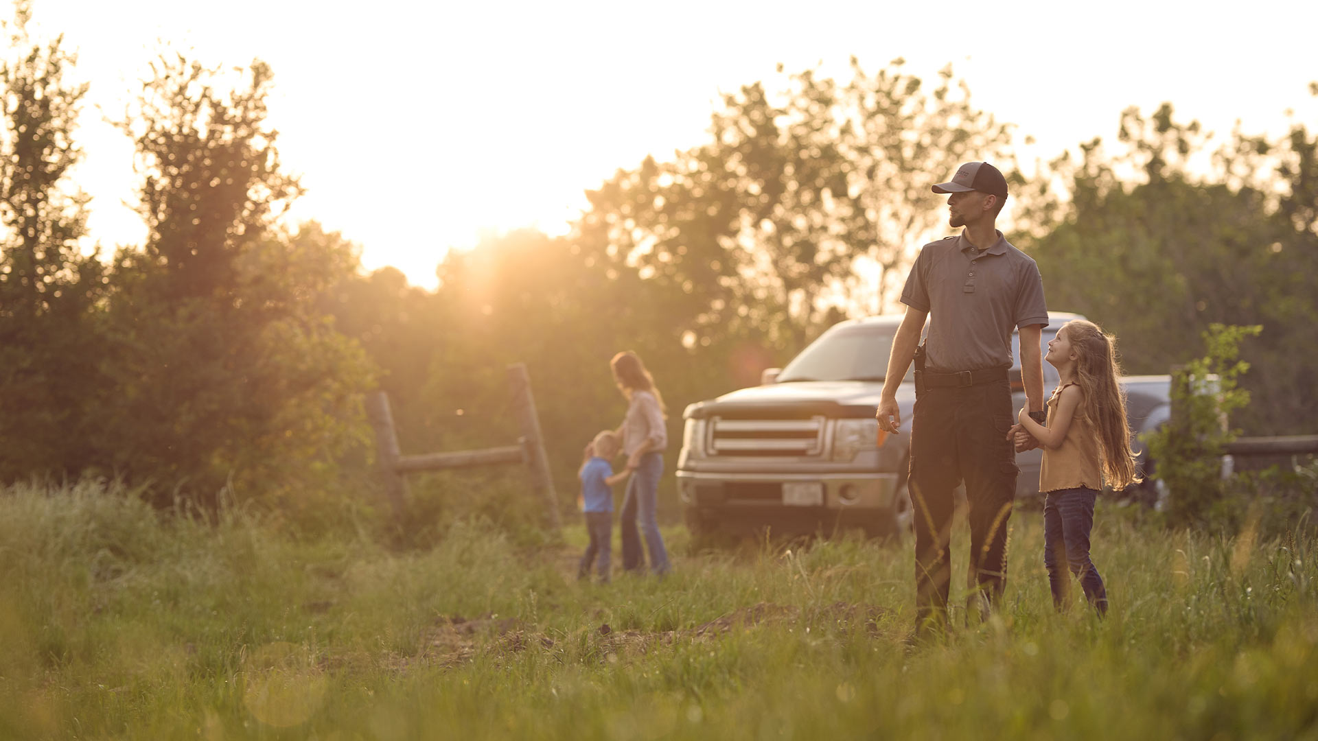 Father, with holstered Staccato handgun, in nature with his family