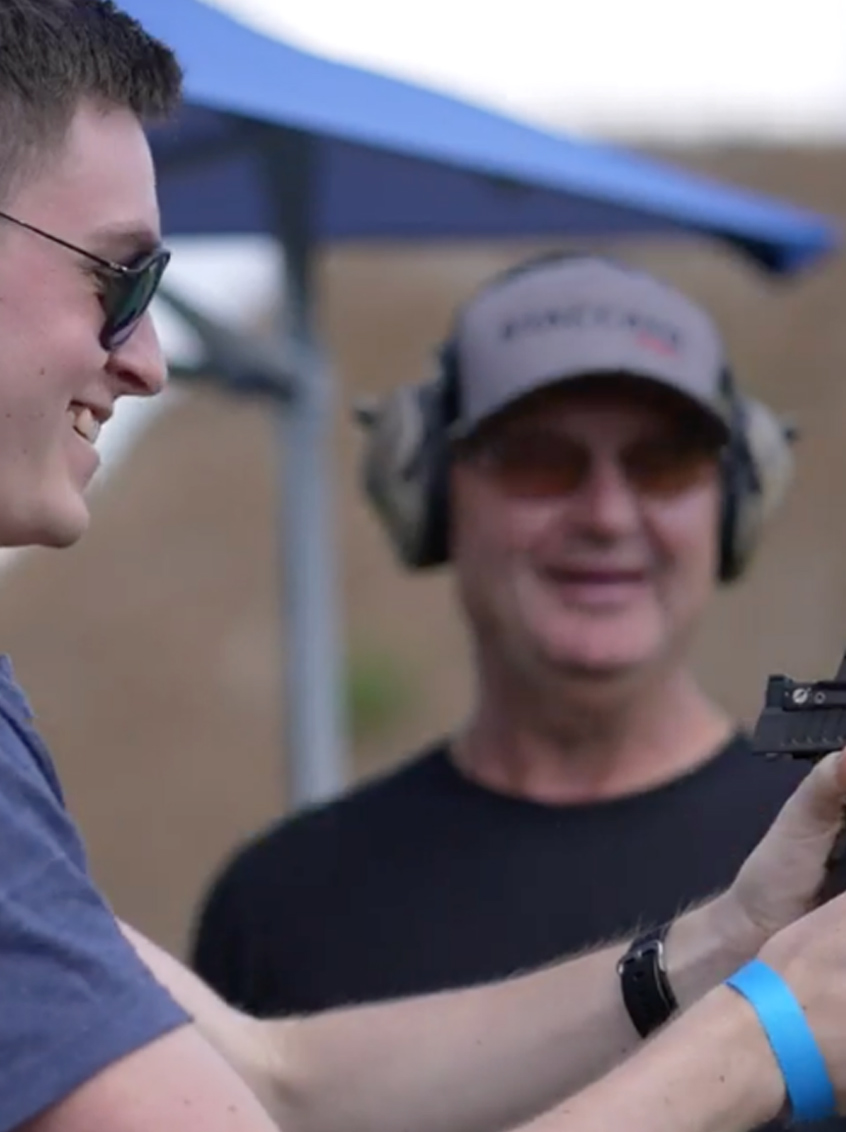 New shooter holding Staccato handgun with instructor in background
