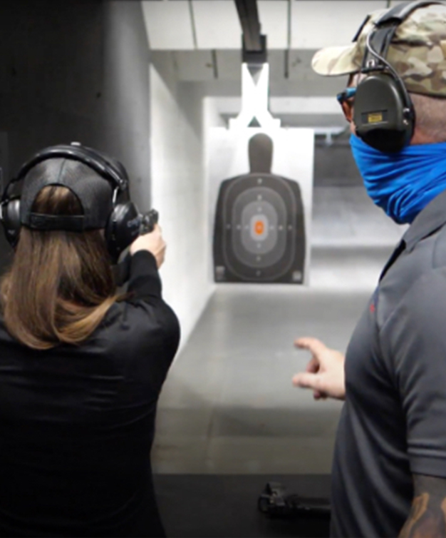 New shooter aiming Staccato handgun down range with instructor advising