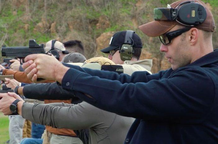 Men in line shooting handgun pistols