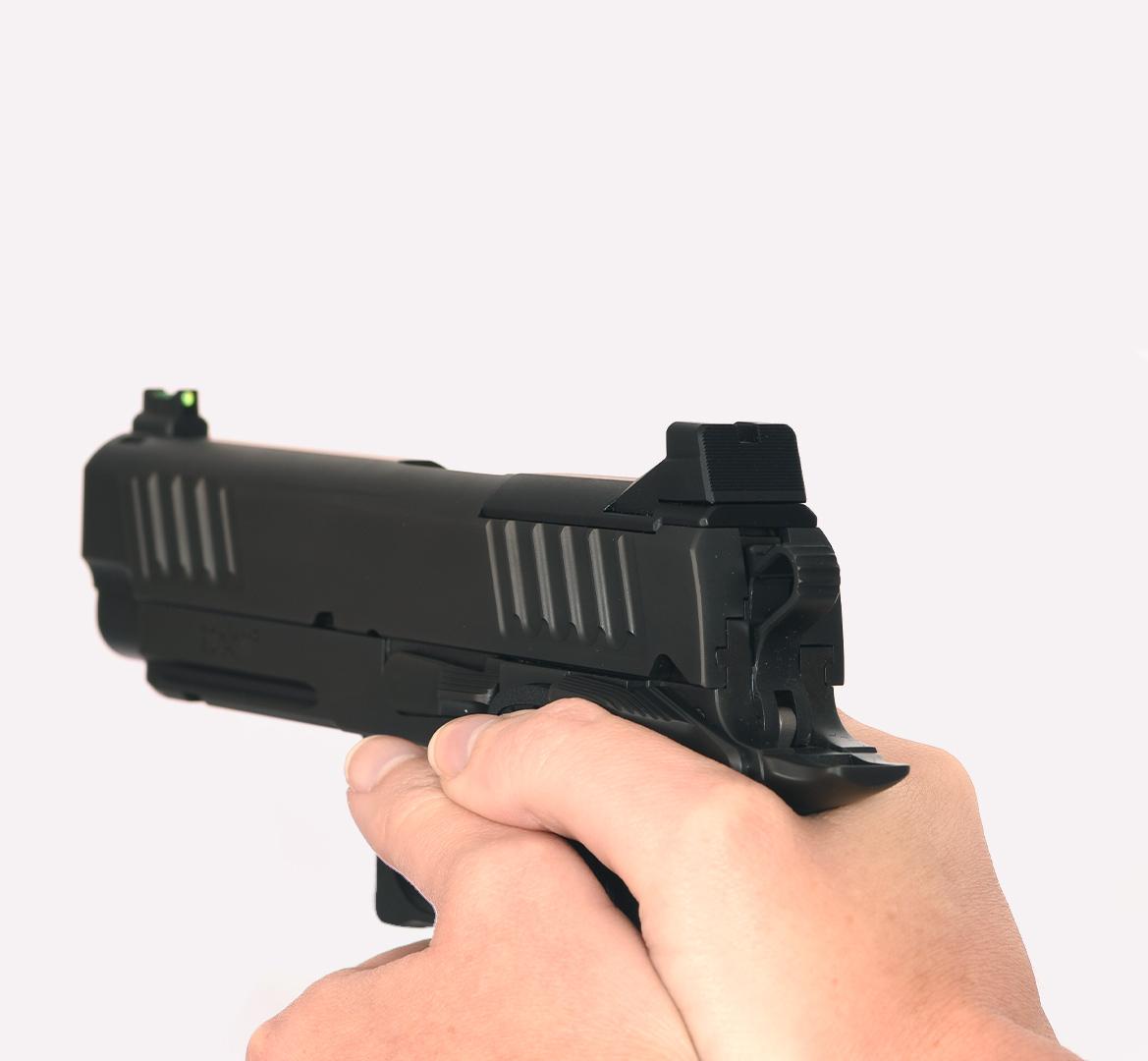 Pair of hands gripping Staccato handgun